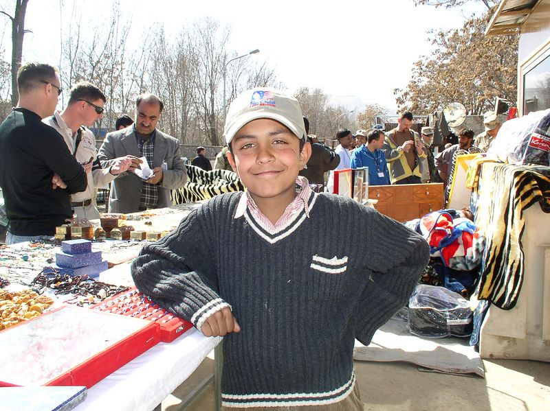 """My good friend Omar Saged at his jewelry stand. He proudly wears a """"Leave No Child"""" hat given to him by lLaura Bush."""