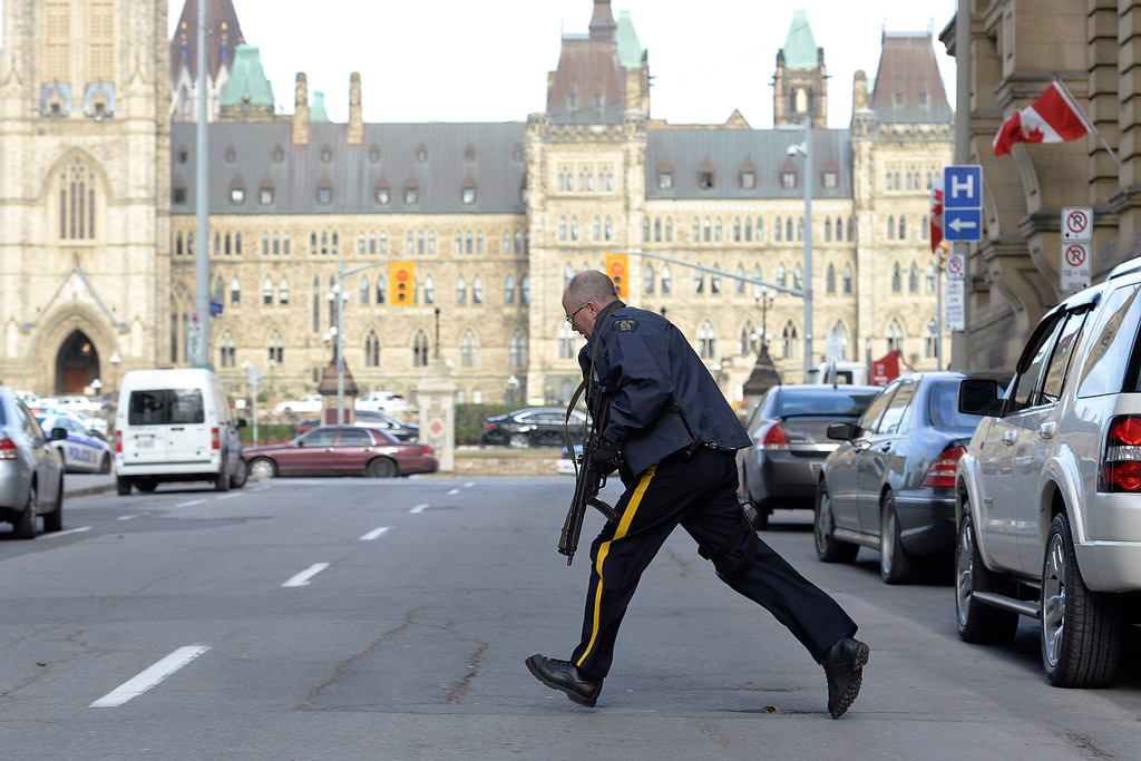 . Police secure an area around Parliament Hill in Ottawa on Wednesday Oct. 22, 2014.  A soldier standing guard at the National War Memorial was shot by an unknown gunman and people reported hearing gunfire inside the halls of Parliament. Prime Minister Stephen Harper was rushed away from Parliament Hill to an undisclosed location, according to officials. (AP Photo/The Canadian Press, Adrian Wyld)
