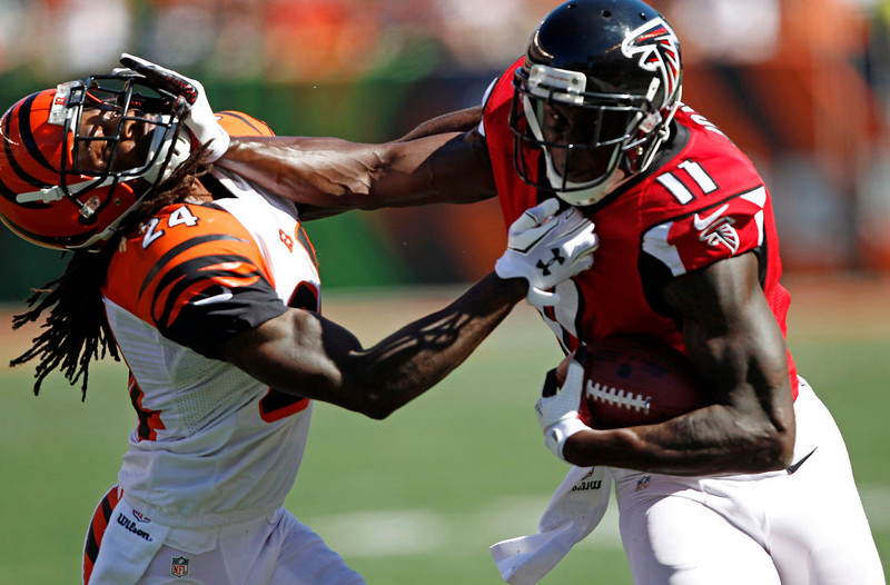 . Atlanta Falcons wide receiver Julio Jones (11) pushes off Cincinnati Bengals cornerback Adam Jones (24) in the second half of an NFL football game, Sunday, Sept. 14, 2014, in Cincinnati. (AP Photo/Frank Victores)