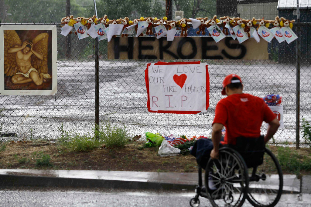 . Tommy Hambicki sits in his wheelchair as he pays his respect at a makeshift memorial for the 19 firefighters who perished battling a fast-moving wildfire in Prescott, Arizona July 1, 2013.    REUTERS/Joshua Lott