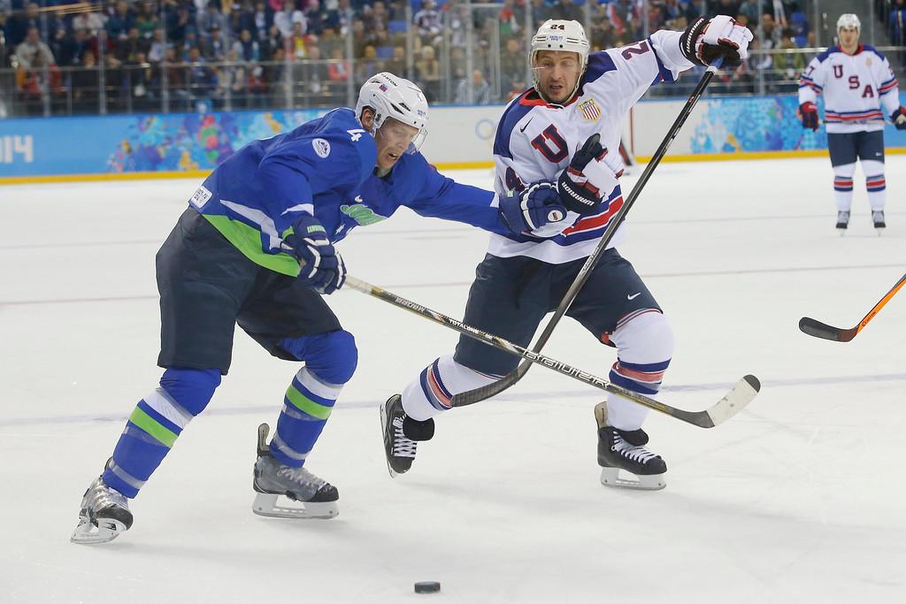 . Slovenia defenseman Andrej Tavzelj battles with USA forward Ryan Callahan for control of the puck during the 2014 Winter Olympics men\'s ice hockey game at Shayba Arena Sunday, Feb. 16, 2014, in Sochi, Russia. (AP Photo/Matt Slocum)