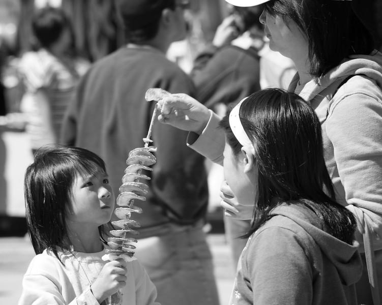 Young girl stares at her potato spring snack 2012 Treasure Island Dragon Boat Festival ref: c0712b98-dd42-42f4-a502-a8fff214a644