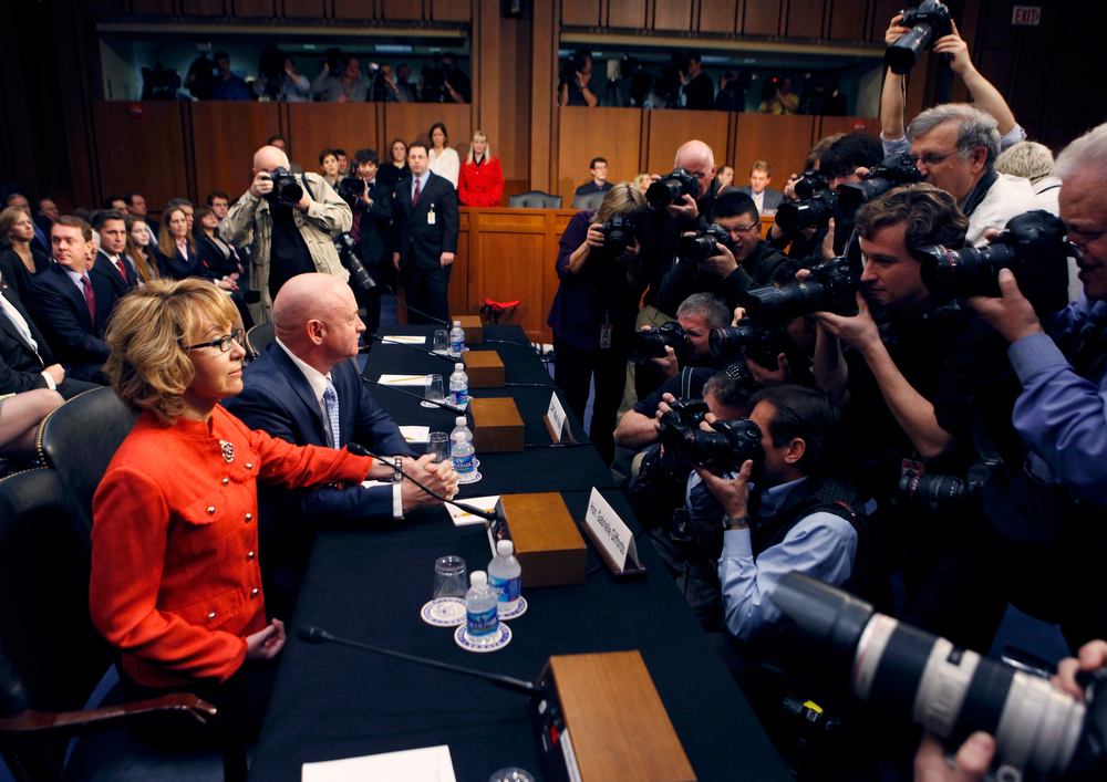 Description of . Former U.S. Rep. Gabrielle Giffords (L) is seated next to her husband, former U.S. Navy Captain Mark Kelly, (C) while news photographers take their pictures prior to a hearing held by the Senate Judiciary committee about guns and violence on Capitol Hill in Washington, January 30, 2013.  REUTERS/Larry Downing