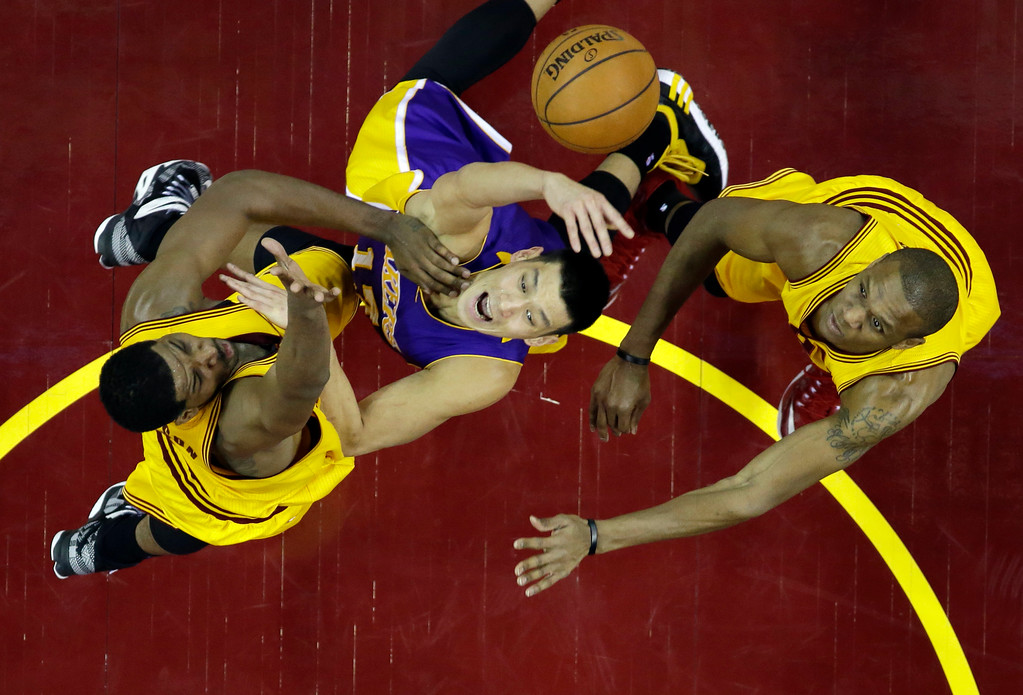 . Los Angeles Lakers\' Jeremy Lin, center, loses the ball against Cleveland Cavaliers\' Tristan Thompson, left, and James Jones in an NBA basketball game Sunday, Feb. 8, 2015, in Cleveland. (AP Photo/Mark Duncan)