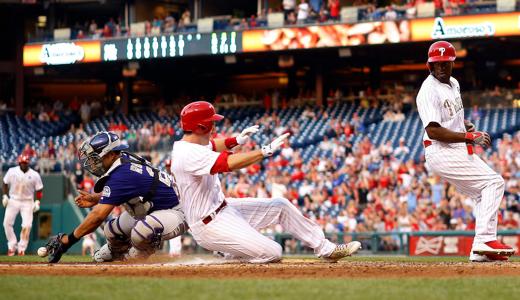 . Philadelphia Phillies\' Jimmy Rollins, right, and Chase Utley, center, score past Colorado Rockies catcher Wilin Rosario on a two-run single by Philadelphia Phillies\' Ryan Howard during the seventh inning of a baseball game, Monday, May 26, 2014, in Philadelphia. Philadelphia won 9-0. (AP Photo/Matt Slocum)