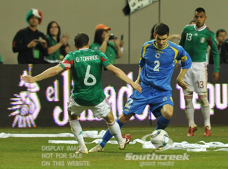 Bosnia-Herzegovina's Defender Mensur Mujdza (#2) makes a move and gets by Mexico's Midfielder Gerardo Torrado (#6) in Soccer action between Bosnia-Herzegovina and Mexico.  Mexico defeated Bosnia-Herzegovina 2-0 in the game at the Georgia Dome in Atlanta, GA.
