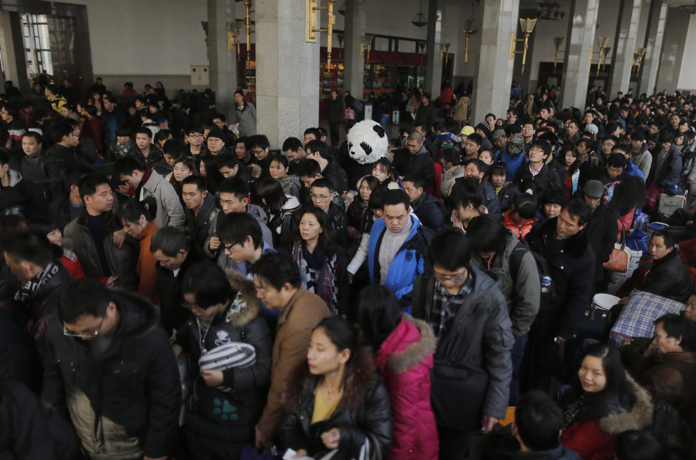 Description of . This picture taken on January 26, 2013, the first day of Spring Festival travel season, shows a lady wearing a panda costume (C) queuing up in the waiting room to get on her train back to Cangzhou in Hefei from Beijing. The lady, together with other three female friends, said she would like to feel the special atmosphere of the Spring Festival traveling in this way.  CHINA OUT     AFP PHOTOSTR/AFP/Getty Images
