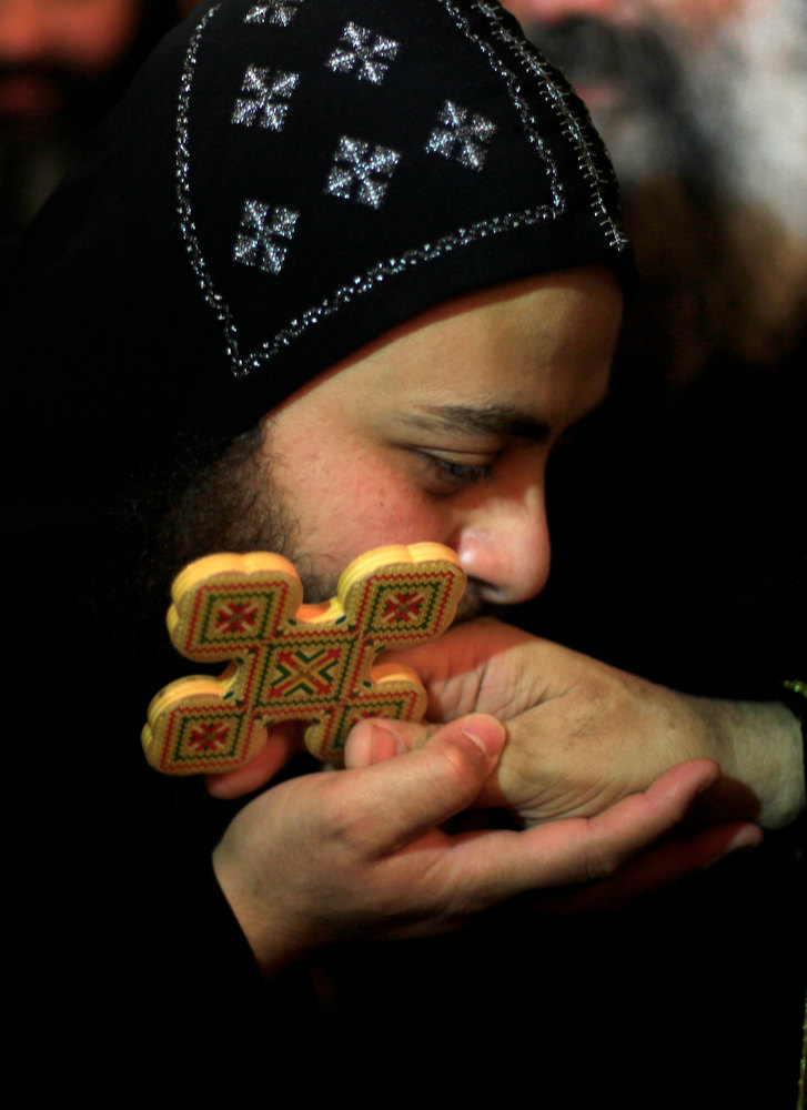 Description of . A clergyman kisses the hand of Egypt\'s Coptic Christian Pope Tawadros II, during an early morning mass at  the historic al-Muharraq Monastery, a centuries-old site some 180 miles (300 kilometers) south of Cairo in the province of Assiut, Egypt, Tuesday, Feb. 5, 2013. Egypt\'s Coptic Christian pope sharply criticized the country\'s Islamist leadership in an interview with The Associated Press on Tuesday, saying the new constitution is discriminatory and Christians should not be treated as a minority. (AP Photo/Khalil Hamra)