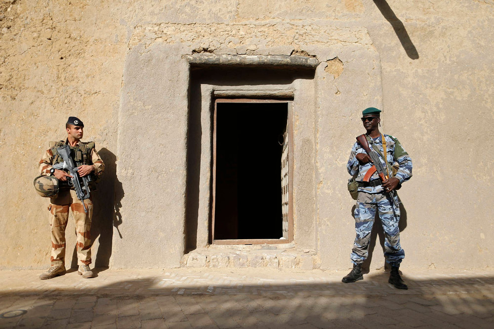 "Description of . A French soldier (L) and a Malian gendarme stand guard at the entrance door of the Djingareiber mosque, in the center of Timbuktu February 2, 2013. Malians chanting ""Thank you, France!\"" mobbed Hollande on Saturday as he visited the desert city of Timbuktu, retaken from Islamist rebels, and pledged France\'s sustained support for Mali to expel jihadists. REUTERS/Benoit Tessier"