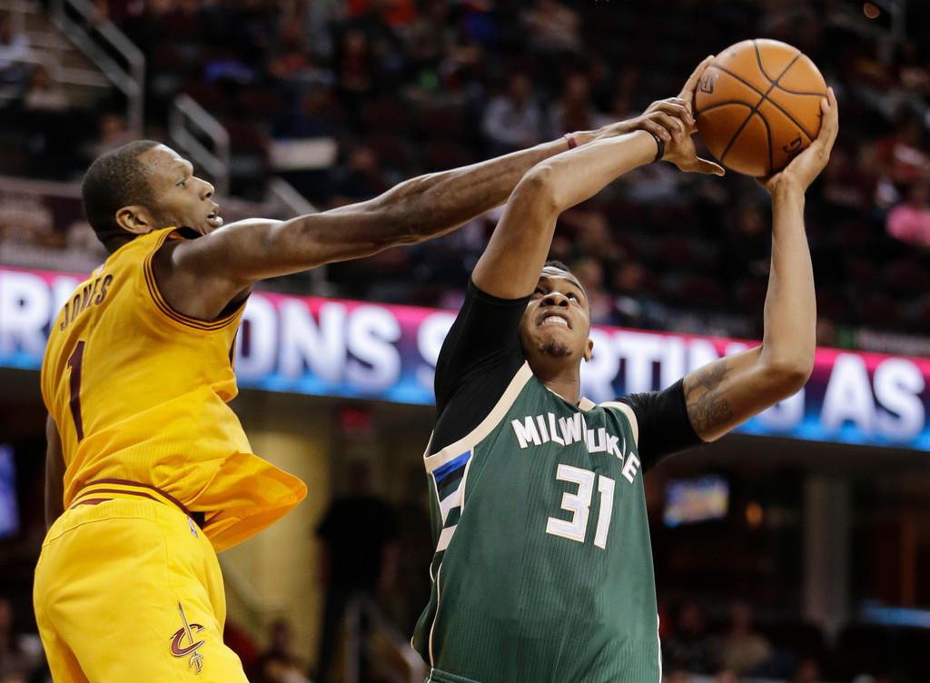 . Milwaukee Bucks\' John Henson (31) shoots around Cleveland Cavaliers\' James Jones (1) in the second half of an NBA preseason basketball game Tuesday, Oct. 13, 2015, in Cleveland. (AP Photo/Tony Dejak)