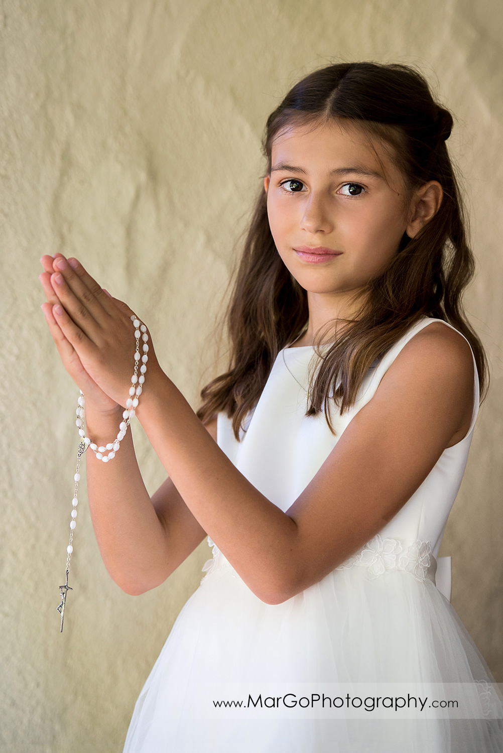 first communion girl in white dress with rosary in folded hands looking into camera at Cafe Wisteria in Menlo Park