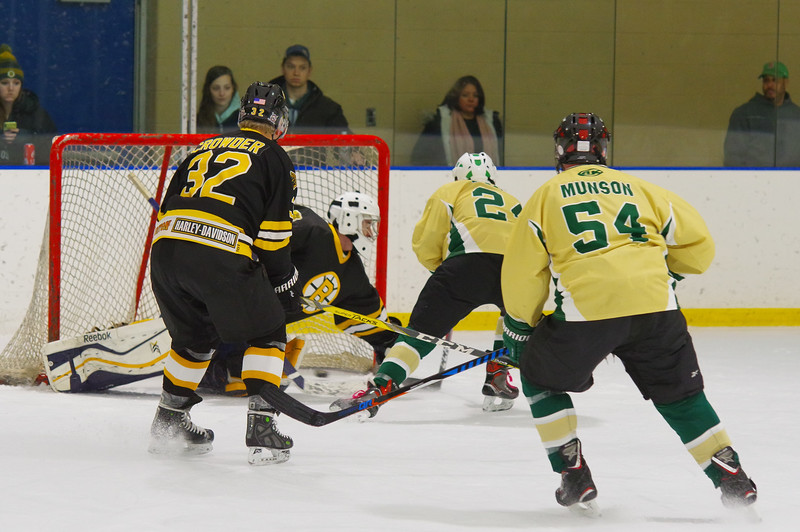 Connor Vasquez (24) makes a move around Bruce Crowder (32 and scores on Bruins Alumni Goalie Shamus Egan (52).