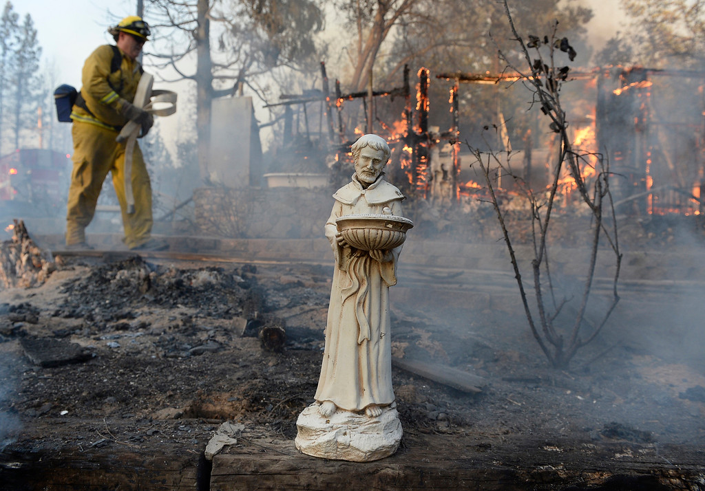 . A religious statue is almost all that is left from a home that burned to the ground on Cedar Drive in Oakhurst,  Calif., Sunday, Sept. 14, 2014, as two raging wildfires in the state forced hundreds of people to evacuate their homes. (AP Photo/The Fresno Bee, Mark Crosse)