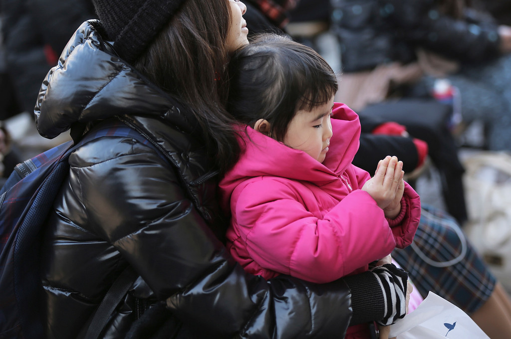 . A girl joins her hands in prayer with her mother to mourn for victims of the March 11, 2011 earthquake and tsunami during a special memorial event in Tokyo Wednesday, March 11, 2015. Still struggling to recover, the tsunami-hit region of northeastern Japan marked the fourth anniversary of the disaster Wednesday with simultaneous moments of silence along the coast. (AP Photo/Eugene Hoshiko)
