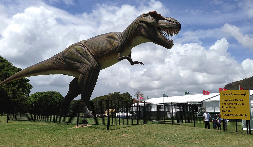 . FILE - In this Dec. 11, 2012 file photo, people stand near an eight-meter (26-foot) replica of a tyrannosaurus rex standing between the 9th green and the 10th tee at the Sunshine Coast resort course in south Queensland, Australia.  The PGA of Australia confirmed, Monday, Feb. 11, 2013,  it will move the venue of its PGA Championship, which was overshadowed last year by the billionaire resort owner\'s decision to position a giant robotic dinosaur outside the clubhouse and post unusual signage around the course. (AP Photo/Dennis Passa, File)