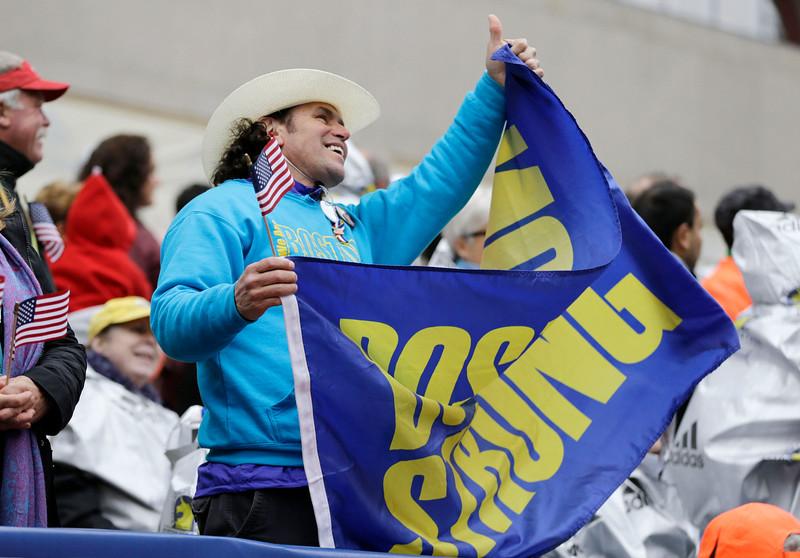 ". Carlos Arredondo, a 2013 Boston Marathon first-responder, holds a \""Boston Strong\"" banner in the grandstand near the Boston Marathon finish line, Monday, April 20, 2015, in Boston. (AP Photo/Elise Amendola)"