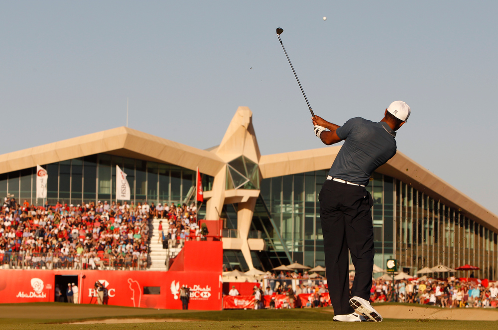 Description of . With the falcon shaped golf clubhouse of Abu Dhabi in the backdrop, Tiger Woods from the U.S. plays a ball on the 18th hole during the second round of Abu Dhabi Golf Championship in Abu Dhabi, United Arab Emirates, Friday, Jan. 18, 2013. (AP Photo/Kamran Jebreili)