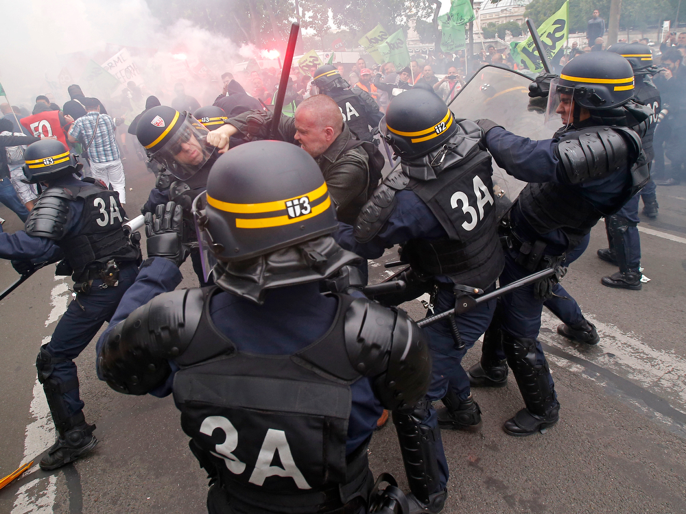 Description of . French riot police clash with a striking train workers, during a protest over a bill to reform the state-run railway system in Paris, Tuesday, June 17, 2014. A weeklong strike by rail workers has caused one of the worst disruptions to the country's rail network in years and is heating up as the reform bill goes to the lower house of Parliament for debate Tuesday. (AP Photo/Michel Euler)