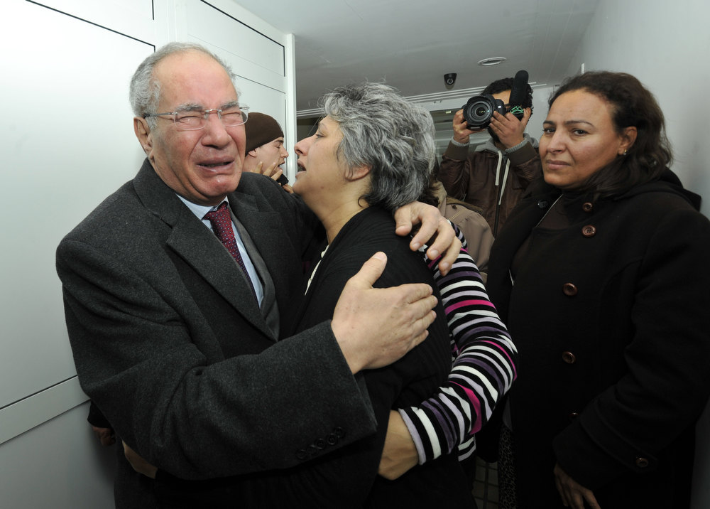 Description of . Human rights activist and lawyer Mokhtar Trifi (L) and Basma Chokri (C), the wife of assassinated Tunisian opposition leader and outspoken government critic Chokri Belaid, mourn over the latter's death after he was shot dead with bullets fired from close range on February 6, 2013, at a clinic in Tunis. President Moncef Marzouki has cancelled his participation in the Organisation of Islamic Cooperation summit in Cairo and is heading back to Tunisia after the murder of opposition leader Chokri Belaid, the presidency said.  His assassination comes at a time when Tunisia is witnessing a rise in violence fed by political and social discontent two years after the mass uprising that toppled the former dictator Zine El Abidine Ben Ali. FETHI BELAID/AFP/Getty Images