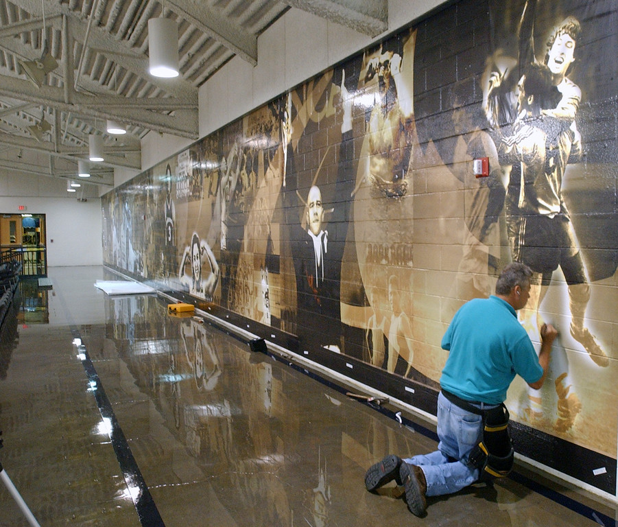 """. Jerry Templeton, who is a subcontractor for Buckeye Decal out of Ohio, checks to make sure that the adhesive holds for the photo mural being placed on a wall inside the Athletics Center, Tuesday, August 22, 2006, on the campus of Oakland University in Rochester, Mich.  OU Athletic Director Greg Kampe said this wall is now called the \""""Wall of History\"""", with the history beginning with Hollie Lepley, the founding father of OU Athletics,  (The Oakland Press/Jose Juarez"""