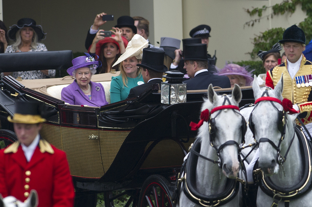 . Britain\'s Queen Elizabeth II (L) arrives on the third day of Royal Ascot, in Berkshire, west of London, on June 20, 2013. The five-day meeting is one of the highlights of the horse racing calendar. Horse racing has been held at the famous Berkshire course since 1711 and tradition is a hallmark of the meeting. Top hats and tails remain compulsory in parts of the course while a daily procession of horse-drawn carriages brings the Queen to the course.  CARL COURT/AFP/Getty Images