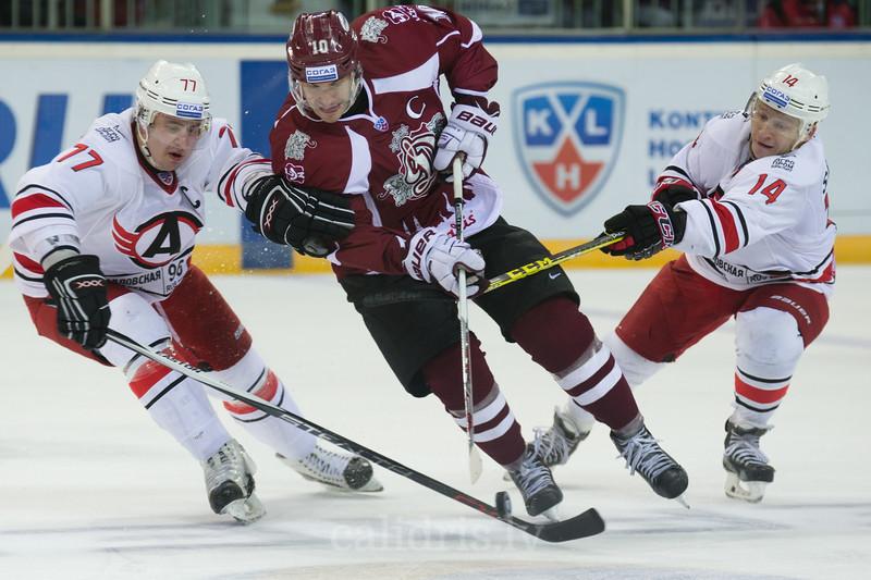Dmitry Megalinsky (77) and Alexei Simakov (14) of Avtomobilist Jekaterinburga tries to stop Lauris Darzins (10)