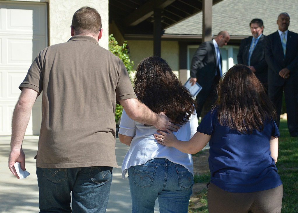 . Ana Hernandez,center, walks back to her house after talking to the media with friends Joshua Rowley and Amy Sharp. Hernandez held a press conference on the front lawn of her home the day after her husband, TSA Behavior Detection Officer Gerardo Hernandez, was killed by a gunman in Terminal 3 at Los Angeles International Airport. Los Angeles, CA. 11/2/2013. photo by (John McCoy/Los Angeles Daily News)