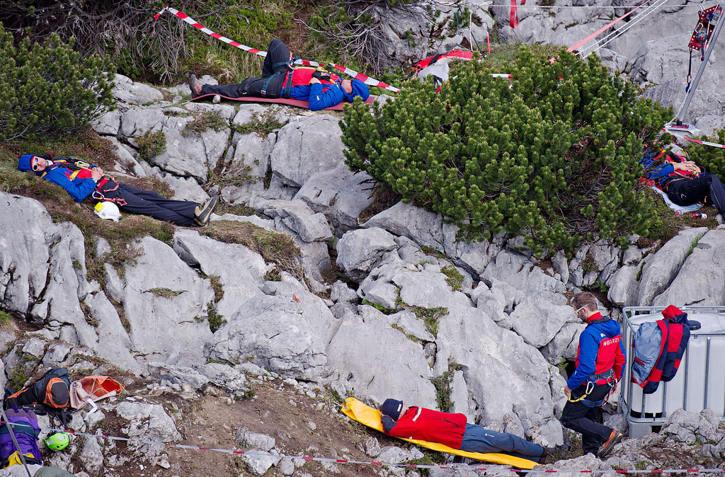 . Mountain rescue workers take a rest on the rocks of mount Untersberg near the mouth of the Riesending cave complex near Marktschellenberg, southern Germany on June 19, 2014, after helping to rescue an injured German speleologist.   AFP PHOTO / DPA/ NICOLAS ARMER /AFP/Getty Images