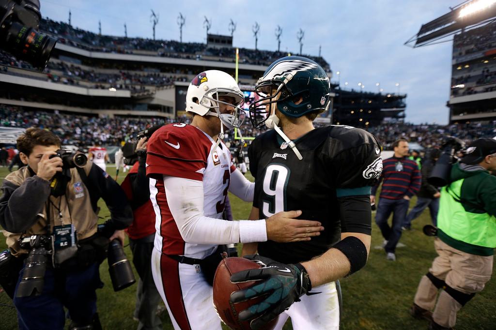 . Arizona Cardinals\' Carson Palmer (3) meets with Philadelphia Eagles\' Nick Foles (9) after an NFL football game on Sunday, Dec. 1, 2013, in Philadelphia. Philadelphia won 24-21. (AP Photo/Matt Rourke)