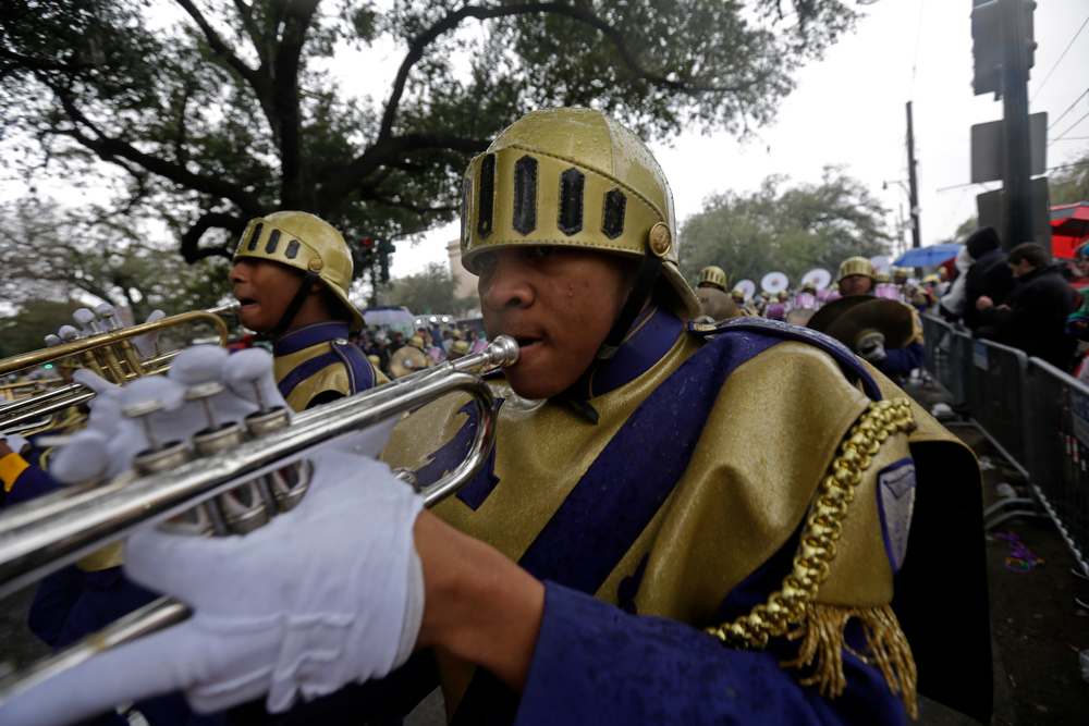 Description of . Members of the St. Augustine High Marching 100 band march in the Krewe of Zulu parade during Mardi Gras day in New Orleans, Tuesday, March 4, 2014. The Zulu parade began on schedule, led by a New Orleans police vanguard on horseback that included Mayor Mitch Landrieu.(AP Photo/Gerald Herbert)