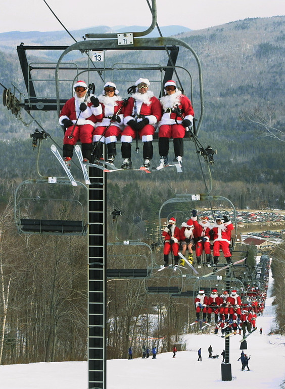 . Skiers and snowboarders dressed as Santa Claus ride up the ski lift, Sunday, Dec. 8, 2002 at Sunday River in Newry, Maine.  About 250 skiers turned up dressed as Santa to ski for free and raise money for the Bethel (Maine) Rotary Club\'s Annual Dinner for Families in Need. (AP Photo/Joel Page)