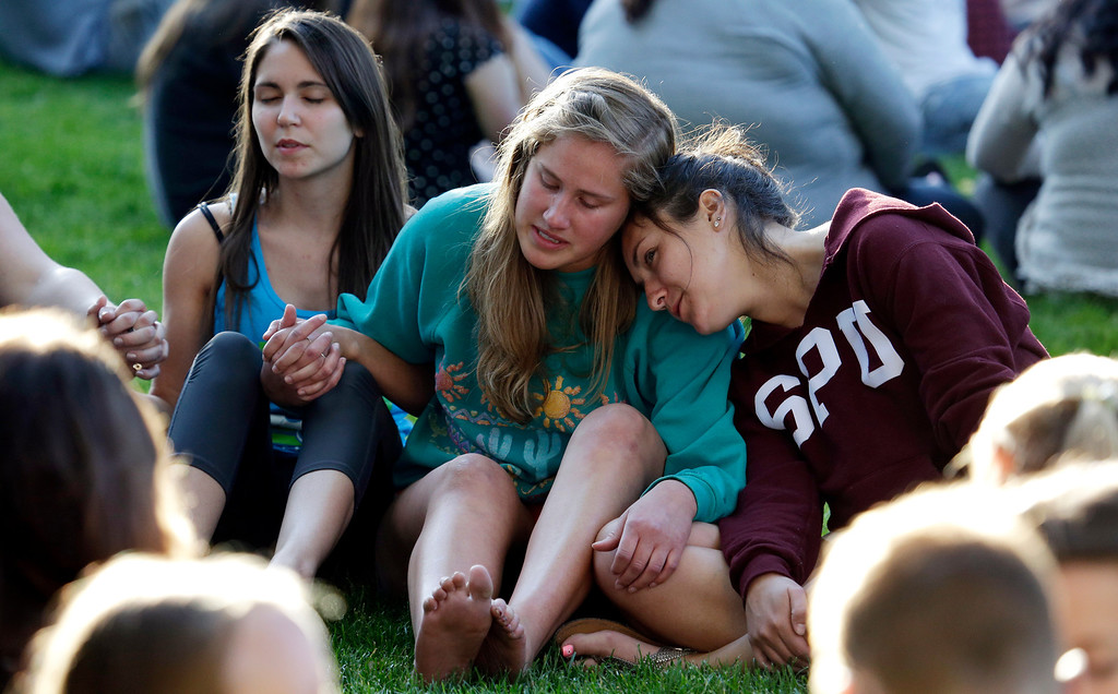 . Students from Seattle Pacific University gather outside in a spontaneous prayer circle after a church service was full, following a shooting on the campus of the university Thursday, June 5, 2014, in Seattle. A lone gunman armed with a shotgun opened fire in a building on the campus, killing one person before he was subdued by a student as he tried to reload, police said. Police say the student building monitor at the university disarmed the gunman and several other students held him until police arrived at the Otto Miller building. (AP Photo/Elaine Thompson)