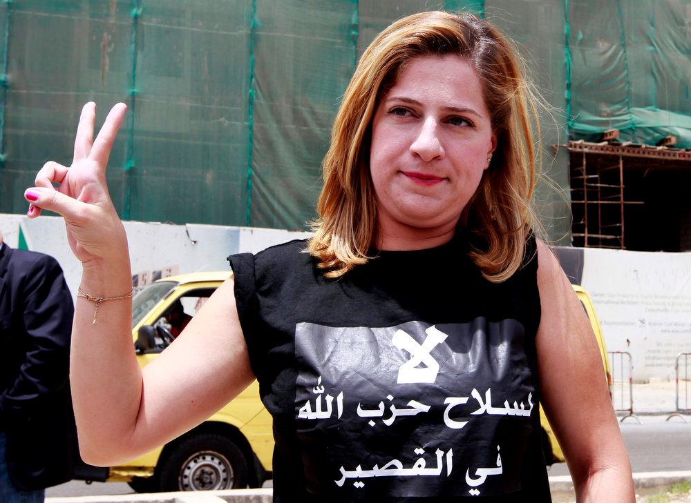 ". A Lebanese activist wearing a shirt with Arabic that reads, ""no to Hezbollah weapons in Qusair,\"" flashes the victory sign, during a protest against the participation of Hezbollah in the Syrian war, at Martyrs square in Beirut, Lebanon, Sunday, June 9, 2013. A senior Lebanese military official says clashes have erupted outside the Iranian embassy in the capital between protesters opposing Hezbollah\'s participation in the Syrian war and unidentified locals, killing one demonstrator. (AP Photo/Bilal Hussein)"