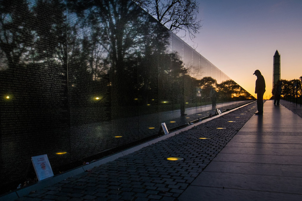 . A visitor at the Vietnam War Memorial in Washington passes early in the morning on Veterans Day, Monday, Nov. 11, 2013, to look at the names inscribed on the wall. Several ceremonies are scheduled in the Nation\'s Capitol to honor those who have served in the U.S. military including a wreath laying at Vietnam War Memorial. The Washington Monument is at right. (AP Photo/J. David Ake)