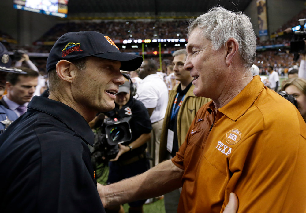 . Oregon State head coach Mike Riley, left, and Texas head coach Mack Brown, right, meet at midfield following then Alamo Bowl NCAA football game, Saturday, Dec. 29, 2012, in San Antonio.  Texas won 31-27. (AP Photo/Eric Gay)