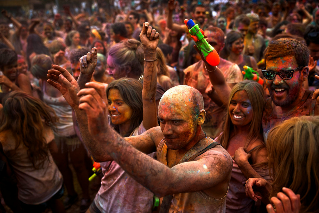 . Revelers of the Holi Festival of Colors dance after throwing colored powders in the air in Madrid, Spain, Saturday, Aug. 9, 2014. The festival is fashioned after the Hindu spring festival Holi, which is mainly celebrated in the north and east areas of India. (AP Photo/Daniel Ochoa de Olza)