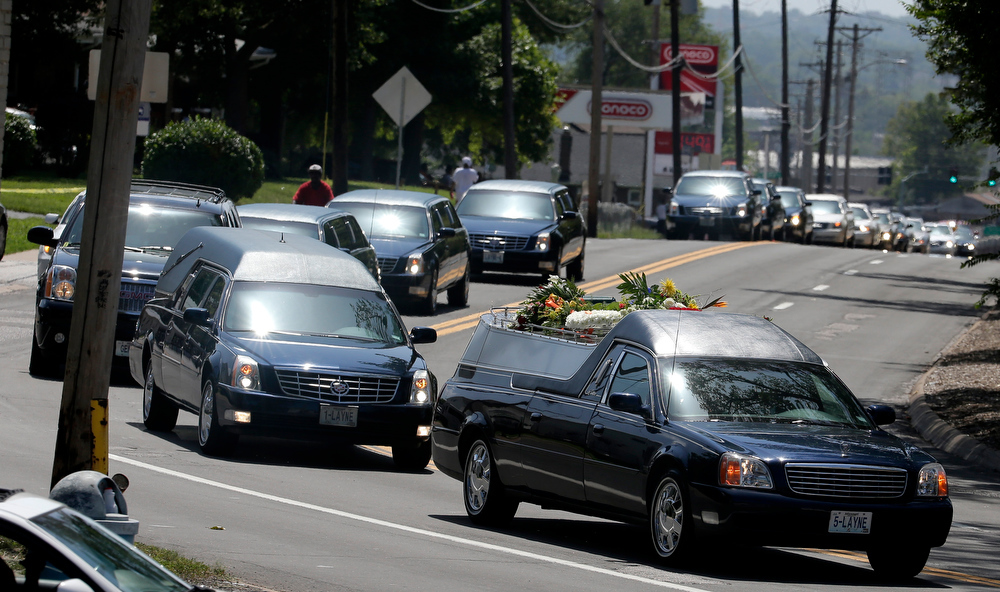 Description of . The funeral procession for Michael Brown heads to the St. Peters Cemetery in Normandy, Mo., Monday, Aug. 25, 2014. Brown, who is black, was unarmed when he was shot in Ferguson, Mo., Aug. 9 by Officer Darren Wilson, who is white. Protesters took to the streets of the St. Louis suburb night after night, calling for change and drawing national attention to issues surrounding race and policing. (AP Photo/Charlie Riedel)