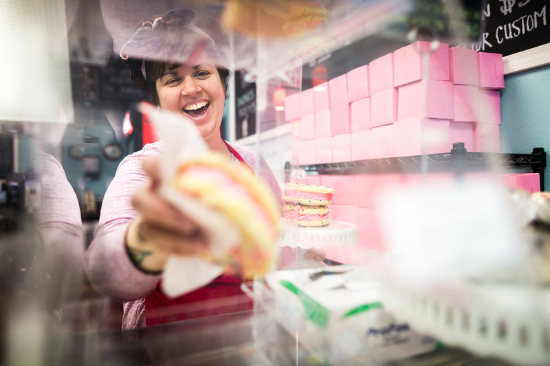 A woman at work handing out frosted cookie sandwiches.