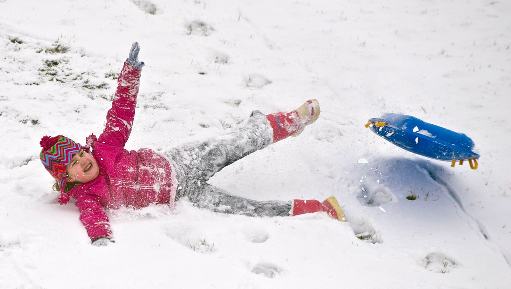 . Emma Erwin, 8, slide down the hill Wednesday, March 6, 2013, behind Danville High School in Danville, Ky. (AP Photo/The Advocate Messenger, Clay Jackson)