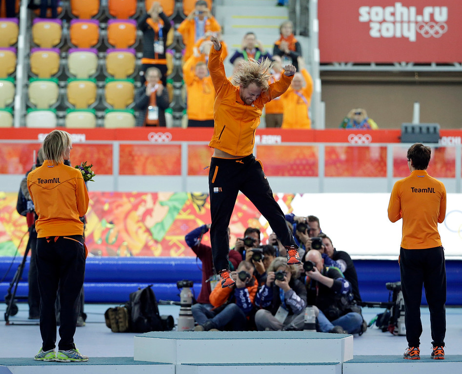 . Silver medallist Jan Smeekens of the Netherlands, right, and bronze medallist Ronald Mulder of the Netherlands, left, watch country athlete and gold medallist Michel Mulder jump in celebration after winning the men\'s 500-meter speedskating race at the Adler Arena Skating Center at the 2014 Winter Olympics, Monday, Feb. 10, 2014, in Sochi, Russia.   (AP Photo/David J. Phillip)
