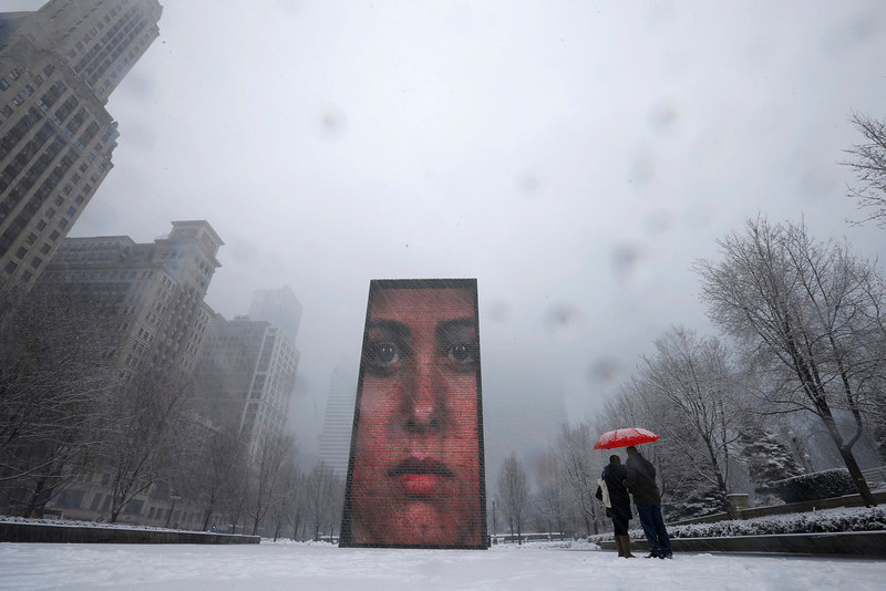 . A couple takes pictures of an LED display on 50-ft tall glass towers, projecting images of faces in Crown Plaza during snow in Chicago March 5, 2013. A deadly late winter storm dumped heavy snow on the Midwestern United States on Tuesday, contributing to numerous highway crashes and flight cancellations as it moved east toward the Ohio Valley and the mid-Atlantic states.  REUTERS/Jim Young