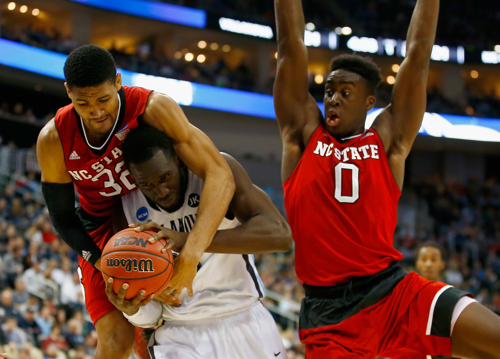 . Daniel Ochefu #23 of the Villanova Wildcats is pressured by Kyle Washington #32 and Abdul-Malik Abu #0 of the North Carolina State Wolfpack in the first half during the third round of the 2015 NCAA Men\'s Basketball Tournament at Consol Energy Center on March 21, 2015 in Pittsburgh, Pennsylvania.  (Photo by Jared Wickerham/Getty Images)