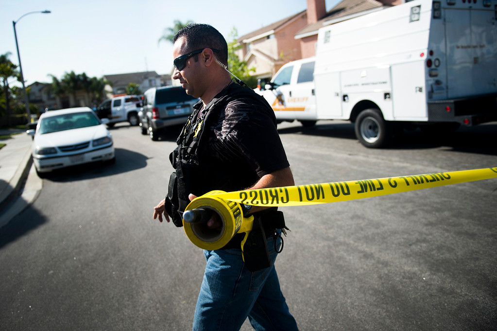 . Sgt. Jesse Dengas puts up a crime scene tape at the scene of a deputy-involved shooting at the 5400 block of Brushwood Court in Chino Hills on Friday, March 28, 2014. (Photo by Watchara Phomicinda/ San Gabriel Valley Tribune)