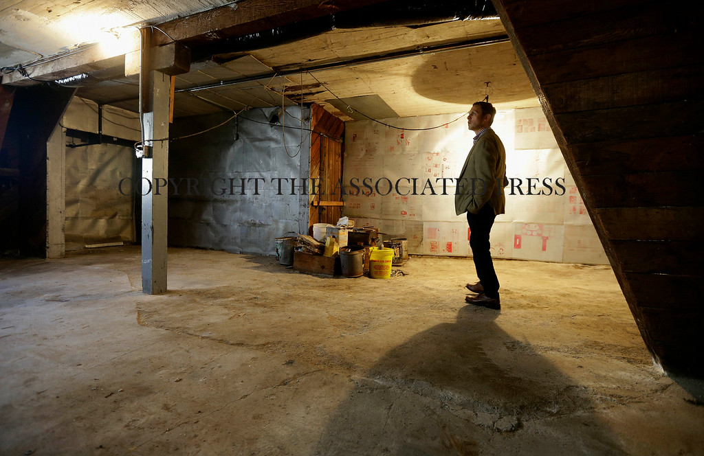 . George Limperis, a realtor with Paragon Real Estate Group, stands in the garage of a property in the Noe Valley neighborhood in San Francisco, Wednesday, July 30, 2014. In the souped-up world of San Francisco real estate a $1 million will barely cover the cost of an 800-square-foot starter home that needs work and may or may not include private parking. (AP Photo/Jeff Chiu)