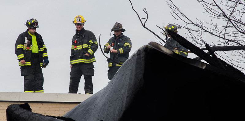 Crews survey the scene of the 6th Alm on Sherman St in Gardner from the roof of an exposure.