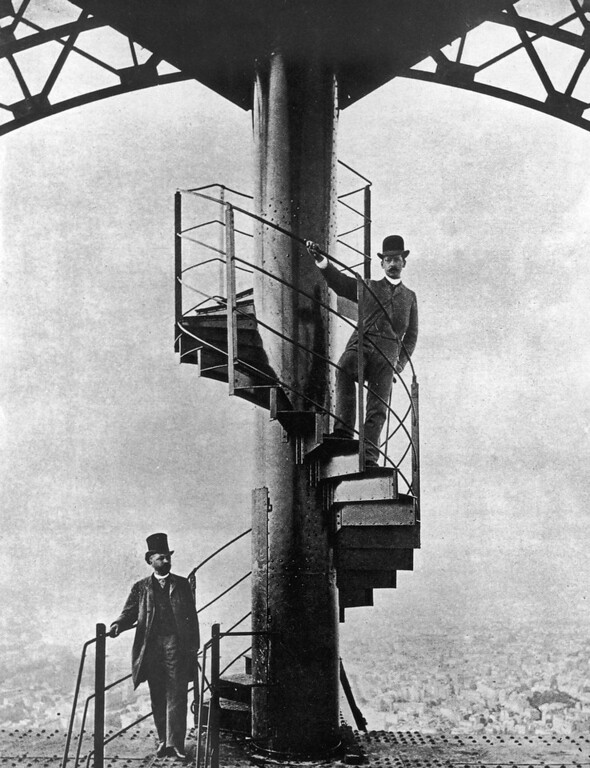 . French engineer Alexandre Gustave Eiffel (1832 - 1923), left, poses high on the steps of the completed Eiffel Tower, which he designed for the 1889 Paris Exposition.     (Photo by General Photographic Agency/Getty Images)