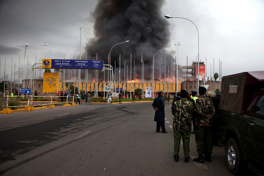 . Policemen stand guard as fire rages at the International arrivals unit  of Jomo Kenyatta International Airport, Nairobi, Kenya, Wednesday, Aug. 7, 2013.  (AP Photo/Sayyid Azim)