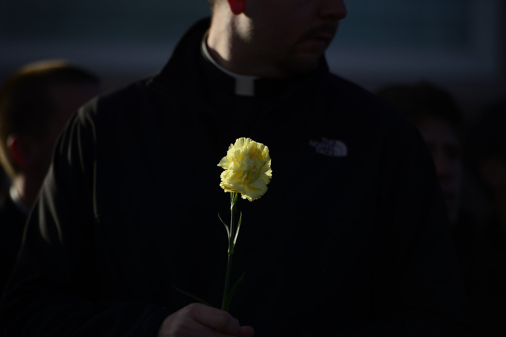 . Seminary student Andrew Kinstetter holds a flower during a protest against Roe vs. Wade at Lighthouse Women\'s Center on Sunday, January 20, 2013. AAron Ontiveroz/The Denver Post