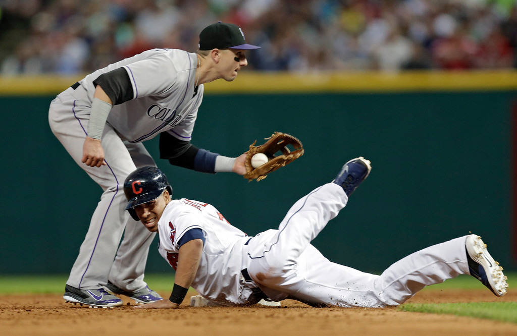 . Cleveland Indians\' Michael Brantley dives safely back into second base as Colorado Rockies shortstop Troy Tulowitzki takes the pickoff throw in the fifth inning of a baseball game Friday, May 30, 2014, in Cleveland. (AP Photo/Mark Duncan)