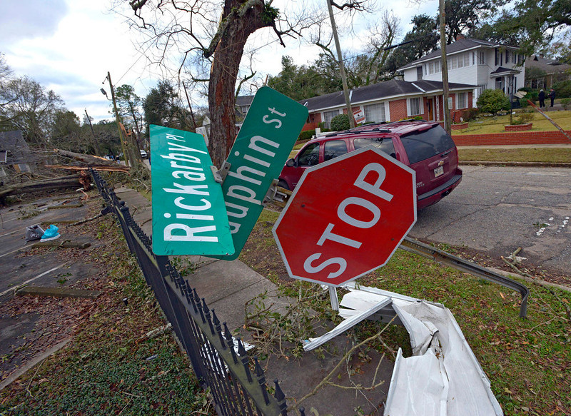 . A street sign is bent at a severe angle from a Christmas Day tornado as residents clean up and assess the damage Wednesday, Dec. 26, 2012  in Mobile, Ala. With only a handful of injuries and no deaths reported statewide from the storms, the head of the state\'s emergency response said it was difficult to fathom how the toll wasn\'t worse. (AP Photo/G.M. Andrews)